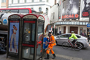 A workman manhandles an arrow traffic sign back on to his lorry in front of a poster for the musical Chicago at the Phoenix Theatre in Charing Cross Road, on 8th October 2018, in London, England.