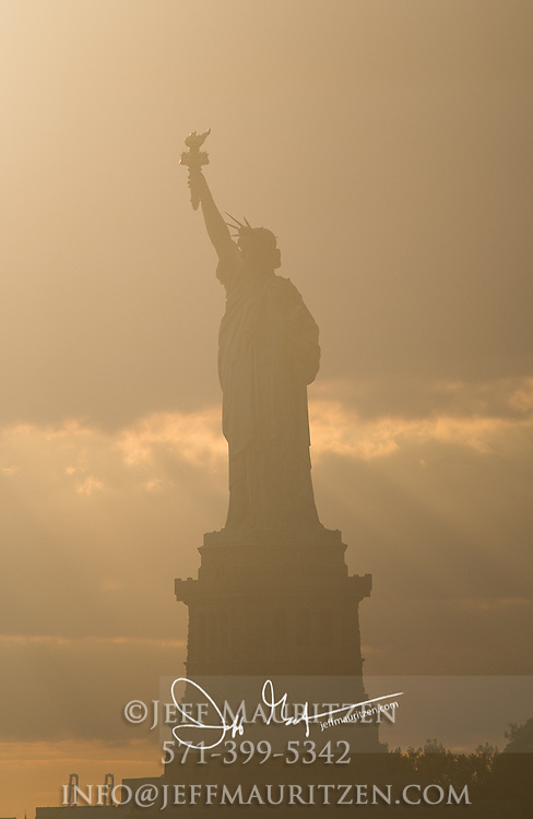 Sunset over the Statue of Liberty over Liberty Island, NYC.