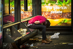 © Licensed to London News Pictures . Manchester , UK . 05/04/2015 . A man sits slumped over in a bus shelter at Piccadilly Bus Station in central Manchester . Revellers on a Saturday night out during the Easter Bank Holiday weekend . Photo credit : Joel Goodman/LNP