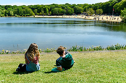 © Licensed to London News Pictures. 20/05/2020. LONDON, UK.  A couple sit by the water as members of the public take advantage of the easing of certain coronavirus pandemic lockdown restrictions to enjoy the sunshine and warm weather at Ruislip Lido in north west London.   The forecast is for temperatures to rise to 29C, the hottest day of the year so far.  Photo credit: Stephen Chung/LNP