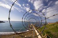 A view of razor wire on top of a chain link fence near a bay in Montana De Oro state park, Morro Bay, California. The fence divides the state park from a nuclear power plant. Since 9/11 security around nuclear power plants has been an issue of concern for both the public and private sectors.