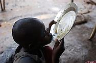 Kiwanya. Congo.  A young boy takes the last drop of food in a refugee camp in Rushuru . Just two miles away in  the little village of Kiwanya, soldier  rebels loyals to General Laurent Nkunda were acused of killing at least twenty people a week ago. (Photo by Miguel Juárez Lugo).