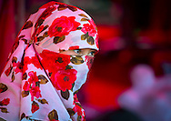 Young Uyghur woman with covered face and colourful headscarf, Xinjiang Uyghur Autonomous Region, China.