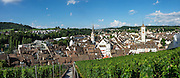 From the Munot fortress, admire a panorama of vineyards and Schaffhausen's Old Town, a patchwork of rooftops and spires, in Switzerland, Europe. Left to right are the church steeples of Münster (first built 1064) and St Johann. This image was stitched from multiple overlapping photos.
