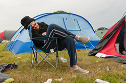 © Licensed to London News Pictures. 12/06/2015. Isle of Wight, UK.  A festival goer sleeps outside his tent at Isle of Wight Festival 2015 on  the morning of  Friday Day 2.  He has been in the same position for hours,  after a late night of enjoyment.      Yesterday the weather was hot and Sunny.  Today rain is forecast.  This years festival include headline artists the Prodigy, Blur and Fleetwood Mac.  Photo credit : Richard Isaac/LNP