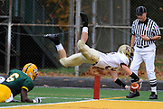 BROOKVILLE, NY - OCTOBER 31, 2009: Kutztown's #32-Anthony Nattle leaps into the air away from the tackle of Post's #6-Detrick Belvin for a third quarter touchdown. C W Post College vs. Kutztown University at C W Post College. Photo by Kathy Kmonicek