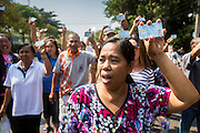 "01 FEBRUARY 2014 - BANGKOK, THAILAND: Thai voters hold up their national ID cards during a march to a polling place to vote. The voters eventually got to the polling place to find that anti-government protestors had forced its closure. Thais went to the polls in a ""snap election"" Sunday called in December after Prime Minister Yingluck Shinawatra dissolved the parliament in the face of large anti-government protests in Bangkok. The anti-government opposition, led by the People's Democratic Reform Committee (PDRC), called for a boycott of the election and threatened to disrupt voting. Many polling places in Bangkok were closed by protestors who blocked access to the polls or distribution of ballots. The result of the election are likely to be contested in the Thai Constitutional Court and may be invalidated because there won't be quorum in the Thai parliament.    PHOTO BY JACK KURTZ"