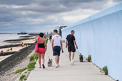 People walking their dogs along the seawall at Canvey Island, Essex