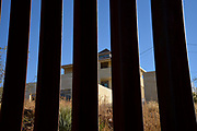 U.S. Border Patrol agent, Vicente Paco, speaks about the work of agents along the international border with Mexico in Nogales, Arizona, USA. Paco indicated that the house in Mexico, seen through the border all from Arizona, is suspected to be a location for illegal border activity.