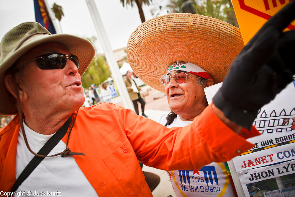 22 OCTOBER 2010 - PHOENIX, AZ:  BILL DEMSKI, from Glendale, AZ, and an opponent of the Tea Party, argues with ARTHUR OLIVAS, right, from Phoenix, a Tea Party supporter. About 300 people attended a Tea Party rally on the lawn of the Arizona State Capitol in Phoenix Friday. They demanded lower taxes, less government spending, repeal of the health care reform bill, and strengthening of the US side of the US - Mexican border. They listened to Arizona politicians and applauded wildly when former Alaska Governor Sarah Palin and her son, Trig, made a surprise appearance. The event was a part of the Tea Party Express bus tour that is crossing the United States.     Photo by Jack Kurtz