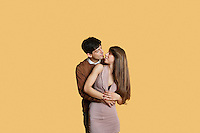 Young man hugging girlfriend from behind over colored background
