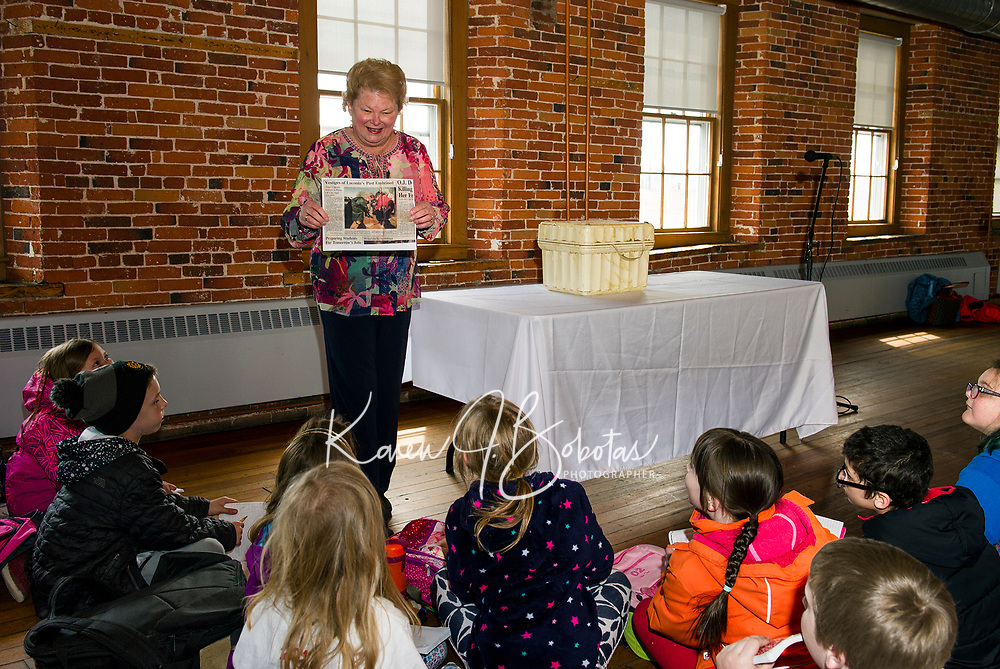 Before opening up the time capsule Pam Clark shows Pleasant Street School 3rd graders the newspaper clipping from when it was buried in front of Laconia City Hall in November of 1993.  (Karen Bobotas/for the Laconia Daily Sun)