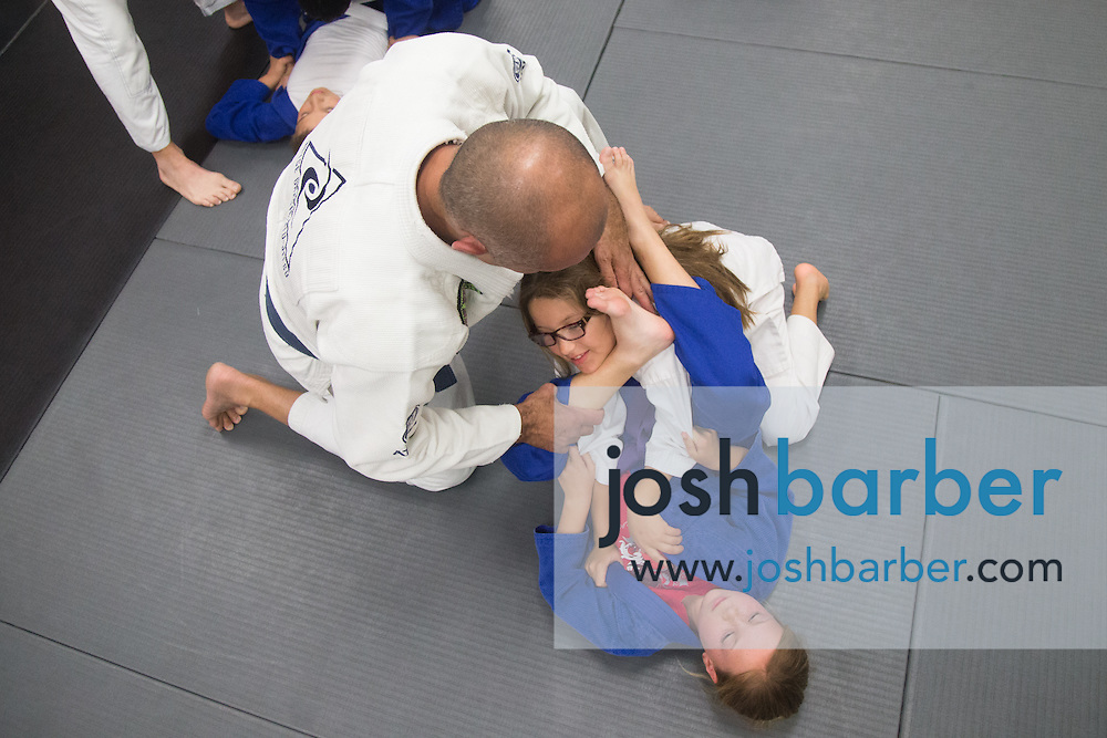 Royc Gracie, Taryn Cagle, bottom, and Iliza Schneider during a jiu-jitsu lesson at US Blackbelt Academy on Thursday, March 26, 2015 in Laguna Niguel, Calif. (Photo/Josh Barber)