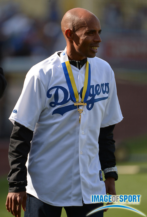 Photo by Kirby LeeMay 8, 2014; Los Angeles, CA, USA; Meb Keflezighi poses with the 2014 Boston Marathon winners medal and a Los Angeles Dodgers jersey before the game against the San Francisco Giants at Dodger Stadium.