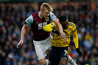 Football - 2019 / 2020 Premier League - Burnley vs. Arsenal<br /> <br /> Ben Mee of Burnley wins an aerial challenge against Alexandre Lacazette of Arsenal, at Turf Moor.<br /> <br /> <br /> COLORSPORT/ALAN MARTIN