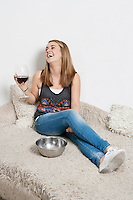 Happy young woman with wine glass sitting on sofa