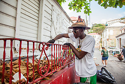 Irvin Mason cleans up trash from a vacant residence.  Residents and volunteers gather for the Garden Street neighborhood cleanup and block Party hosted by E's Garden and Things, Long Path/Garden Street Community Association, and the Economic Development Authority's Enterprise and Commerical Zone Commission.  St. Thomas, USVI.  5 September 2015.  © Aisha-Zakiya Boyd