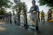 "01 FEBRUARY 2014 - BANGKOK, THAILAND: Thai police in formation to keep voters and protestors apart near the Din Daeng polling station in Bangkok. Thais went to the polls in a ""snap election"" Sunday called in December after Prime Minister Yingluck Shinawatra dissolved the parliament in the face of large anti-government protests in Bangkok. The anti-government opposition, led by the People's Democratic Reform Committee (PDRC), called for a boycott of the election and threatened to disrupt voting. Many polling places in Bangkok were closed by protestors who blocked access to the polls or distribution of ballots. The result of the election are likely to be contested in the Thai Constitutional Court and may be invalidated because there won't be quorum in the Thai parliament.    PHOTO BY JACK KURTZ"