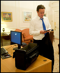 The Prime Minister David Cameron checks his mobile and Blackberry in his office on the night he became Britain's new Prime Minister, Tuesday May 11, 2010, Photo By Andrew Parsons/i-Images