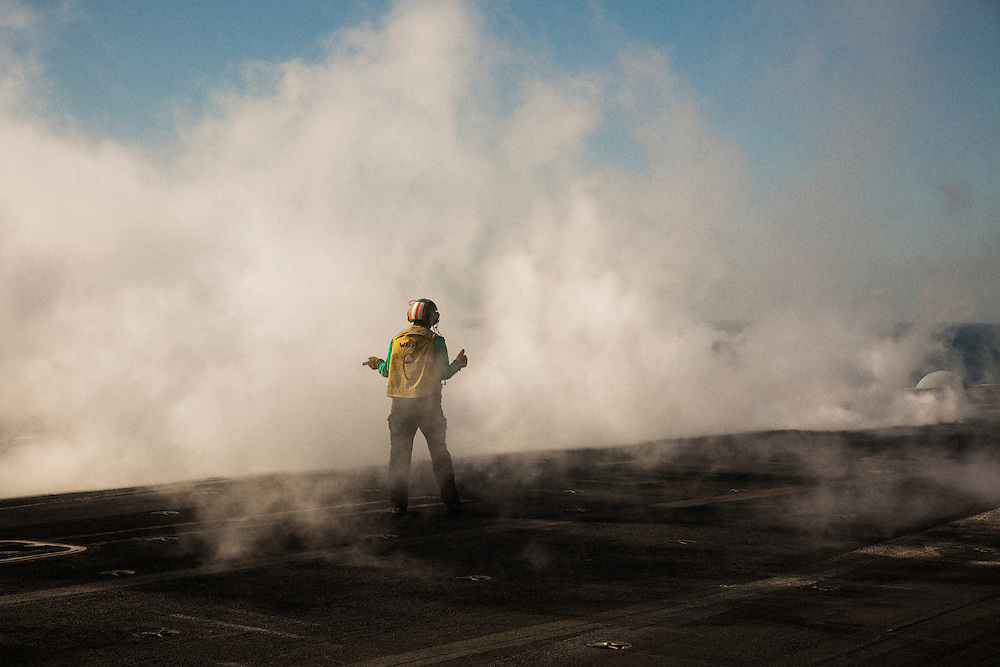 A catapult officer walks through the steam rising immediately after the launch of an aircraft<br /> <br /> Aboard the USS Harry S. Truman operating in the Persian Gulf. February 25, 2016.<br /> <br /> Matt Lutton / Boreal Collective for Mashable