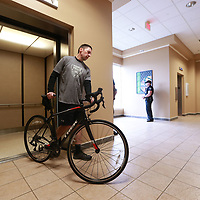 Tupelo Police Officer Bruce Dodson rolls his bicycle off the elevator at Tupelo City Hall to announce he is riding in this year's law enforcement bike ride in Washington D.C in memory of Tupelo Police Sgt. Gale Stauffer.
