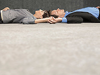 Business man and woman lying on ground head to head holding hands side view