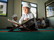 10 JULY 2015 - BANGKOK, THAILAND: Boys studying the holy Qur'an (Koran) before Iftar at Haroon Mosque in Bangkok. Iftar is the evening meal when Muslims end their daily Ramadan fast at sunset. Iftar is a communal event at Haroon Mosque and hundreds of people usually attend the meal.     PHOTO BY JACK KURTZ