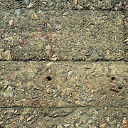 Inside the Miraflores Locks on the southern end of the Panama Canal. A close-up of the concrete walls of the Canal with a mix of concrete, seashells, and stones. Opened in 1914, the Panama Canal is a crucial shipping lane between the Atlantic and Pacific Oceans that mean that ships don't have to go around the bottom of South America or over the top of Canada. The Canal was originally built and owned by the United States but was handed back to Panama in 1999.