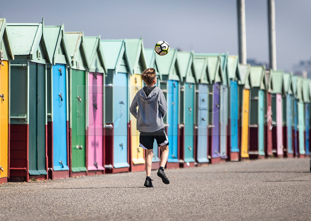 © Licensed to London News Pictures. 22/04/2019. Brighton and Hove, UK. A youth plays football in front of multi-coloured beach huts on the Western Esplanade at Hove, West Sussex. Most of the UK is enjoying record breaking high Easter weekend temperatures. Photo credit: Peter Macdiarmid/LNP