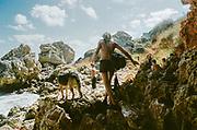 Woman and dog climbing rocks by the water, BulgariaTek, Bulgaria, August 2011
