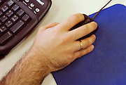Male hand holding a computer mouse near a black keyboard