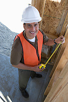 Construction worker measuring wall with measure taper inside half constructed house
