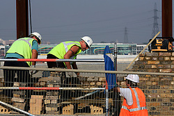 UK ENGLAND LONDON 17AUG05 - Construction workers repair a wall in Stratford, surrounding the site of the planned Olympic Stadium and Village for the 2012 London Olympic Games. Winning the bid against rival Paris, the London Games are expected to return a £ 100 million surplus to the IOC and British sport...jre/Photo by Jiri Rezac ..© Jiri Rezac 2005..Contact: +44 (0) 7050 110 417.Mobile:  +44 (0) 7801 337 683.Office:  +44 (0) 20 8968 9635..Email:   jiri@jirirezac.com.Web:    www.jirirezac.com..© All images Jiri Rezac 2005 - All rights reserved.