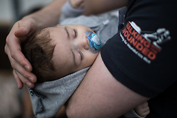 © Licensed to London News Pictures . 04/09/2017 . Manchester , UK . Resident DAVID SEVILLE (33) with his son DAVID SEVILLE JUNIOR (four months) out playing in the street as Prince Harry visits the Walking With the Wounded ( WWTW) hub on Canada Street , Newton Health .  WWTW helps ex-service personnel with physical or mental health needs make the transition back to civilian life . The street was subject to an episode of DIY SOS when people gave their time and resource to help redevelop the houses . Photo credit : Joel Goodman/LNP