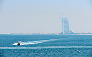 Family in speedboat at speed on sea with Burj Dubai hotel in background.