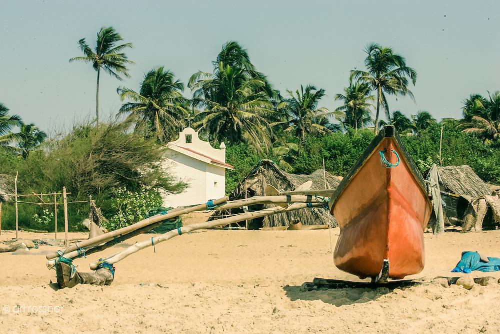 Orange small boat on the beach.