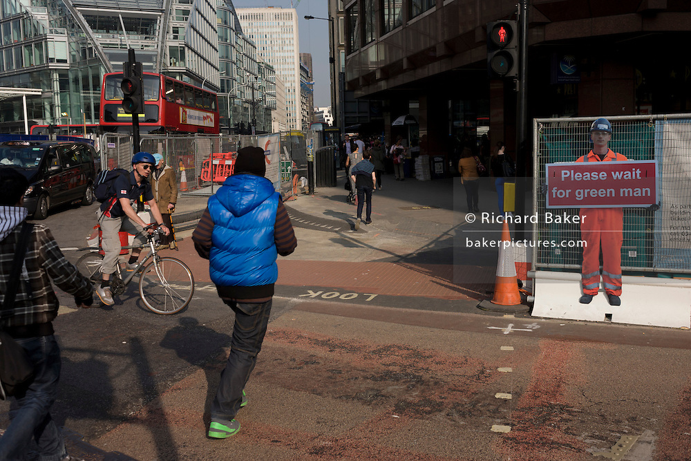 Young men dash in front of approaching cyclist at a crossing in central London near miniature workman warning.