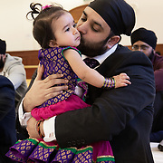 Hounslow, Greater London, UK, January 25, 2015. Sikh Temple Gurdjwara Sri Guru Singh Sobha. <br /> Sandeep, Ashreena's father, embraces his daughter during the religious ceremony to celebrate her 1st birthday. Unlike what usually happens in the Indian community, where even today daughters are not celebrated, Gurmeet and her husband Sandeep, decided to give a big party for wishing a happy birthday to their daughter and blessing girls in general.