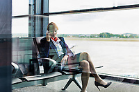Photo of young attractive airport staff sitting while talking on smartphone