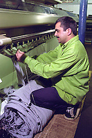 Machinist operating a knitting machine....