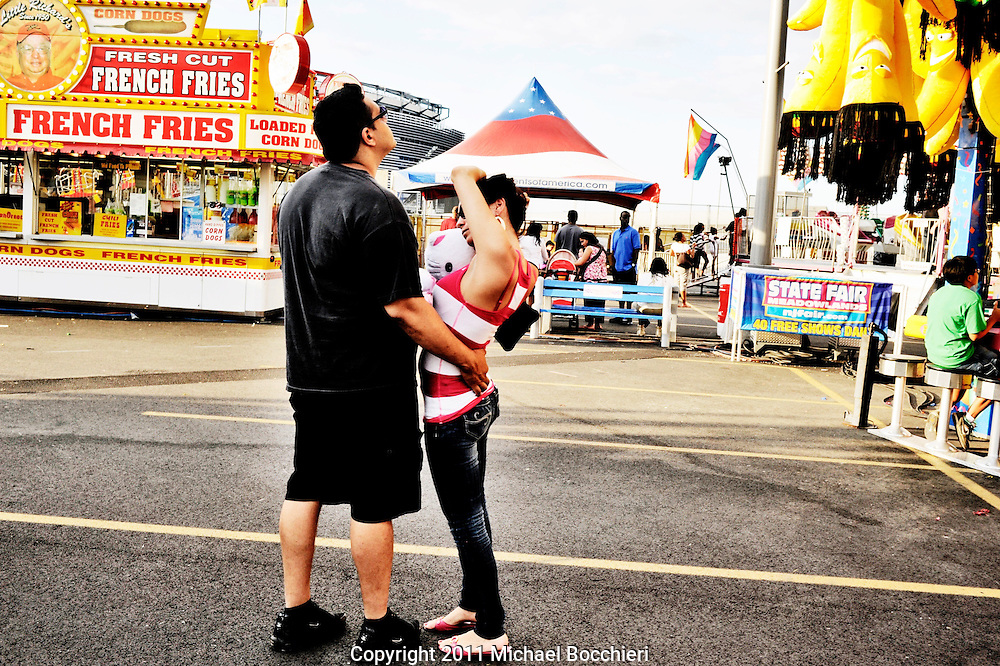 EAST RUTHERFORD, NJ - July 01:  A couple share a moment at the State Fair at the New Meadowlands Fairgrounds on July 01, 2011 in EAST RUTHERFORD, NJ.  The first Fair at the Meadowlands opened in 1986 as a 6-day event encompassing 10 acres offering a dozen rides and games. Today State Fair Meadowlands at Giants Stadium Fairgrounds is the largest in New Jersey and in the NY Metro area encompassing 35 acres, featuring over 150 rides and attractions plus over 75 food vendors from around the country.  (Photo by Michael Bocchieri/Bocchieri Archive)