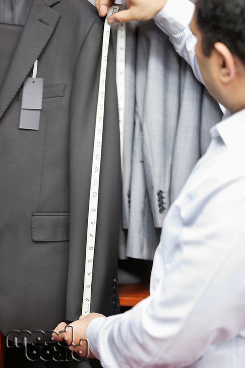 Tailor taking measurement of suit's sleeve