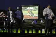 Goshen, New York - People stand around the track, which is lined with luminaria in remembrance of cancer victims, and sit on the grass to watch a video projected onto a large screen during the Relay for Life at Goshen High School on June 19, 2011. The Relay for Life is the American Cancer Society's signature fundraising event. Participants celebrate the lives of people who have battled cancer, remember loved ones lost, and fight back against the disease by raising money.