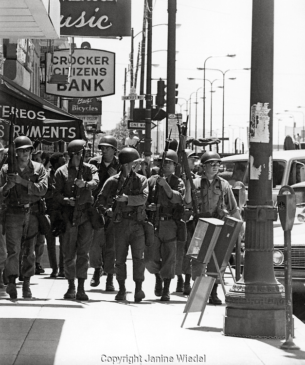 US National guard soldiers with riffles and bayonets take over The University of California as well as the town of Berkeley during The  People's Park student protest & riots in  1969.