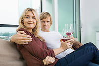 Portrait of smiling couple with wine glasses in living room at home