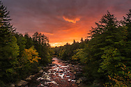 The morning sun lights both the sky and Blackwater River on fire with orange and red hues, while the trees begin to show their autumn colors.  West Virginia.