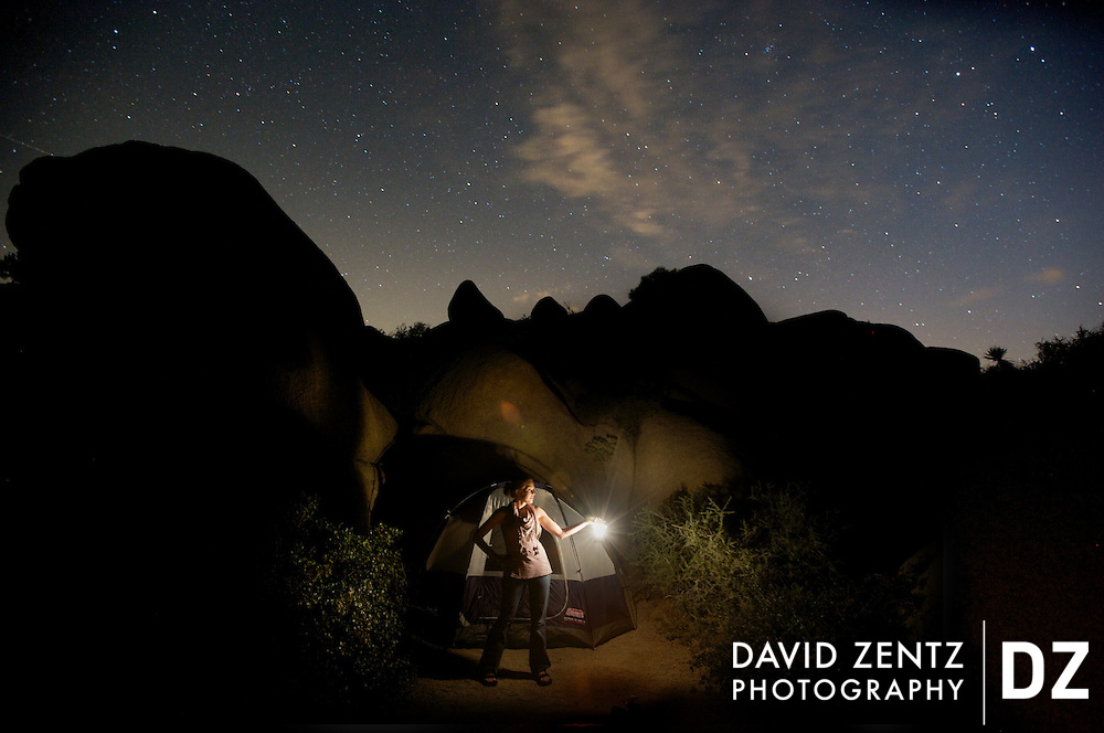 A woman holds a lantern while standing in a campsite beneath a starry sky at the Jumbo Rocks campground in Joshua Tree National Park, Calif.