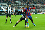 Wilfried Zaha (#11) of Crystal Palace defends the ball from the challenge of Javi Manquillo (#19) of Newcastle United during the Premier League match between Newcastle United and Crystal Palace at St. James's Park, Newcastle, England on 21 December 2019.