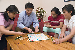 Three generations of family playing a game of scrabble together at home,