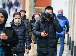 © Licensed to London News Pictures. 31/01/2020. Manchester , UK . A man wears a protective mask as he walks in Central Manchester. Two people in the same family have been diagnosed with the Coronavirus in the UK, which has killed at least 213 people in China Photo credit: Ioannis Alexopoulos /  LNP